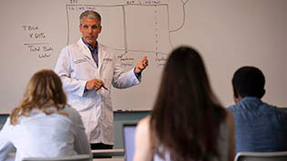 Group of doctors in white lab coats reviewing information on a whiteboard.