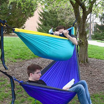Students studying while hammocking.