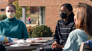 Female students sitting at a table outside.
