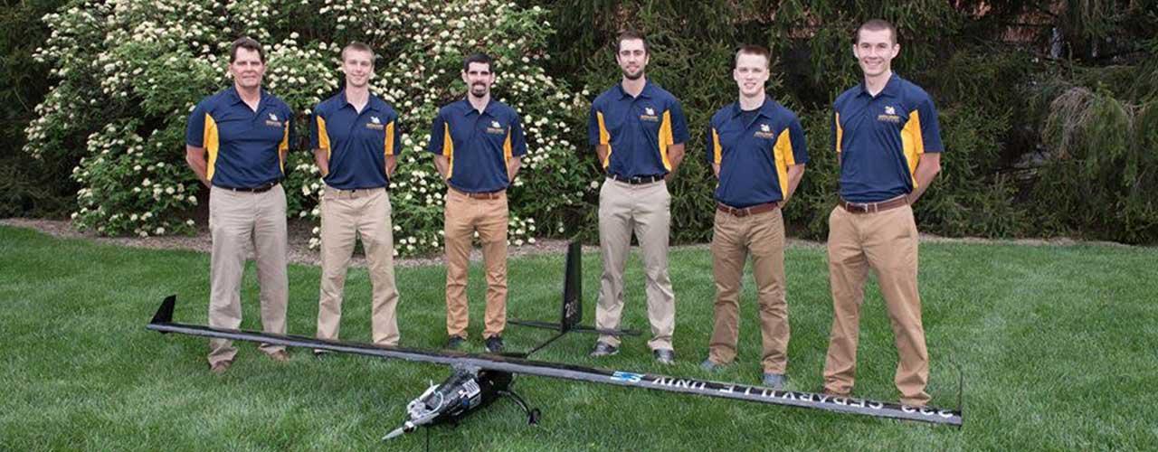 SAE Aero Design team poses behind award-winning plane
