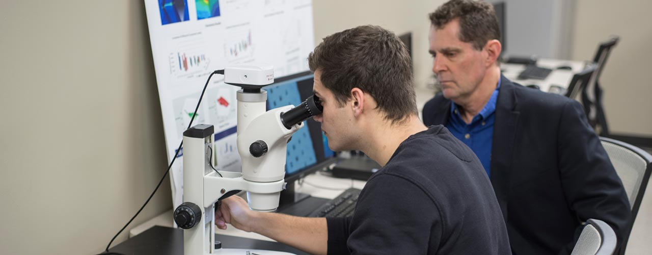 Biomedical engineering student looks at 3D printing structure through microscope