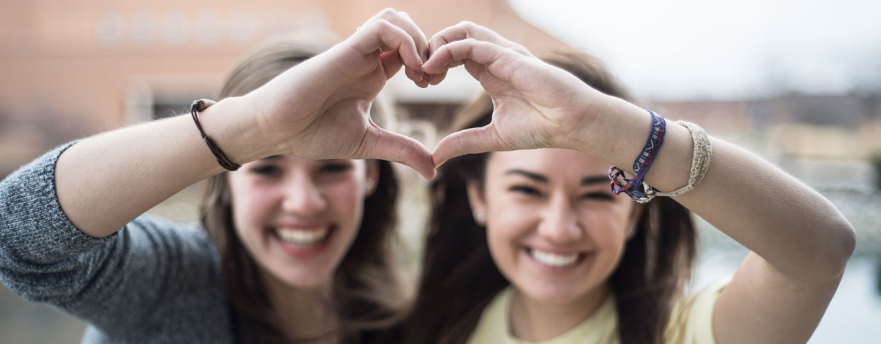 Students make heart shape with hands