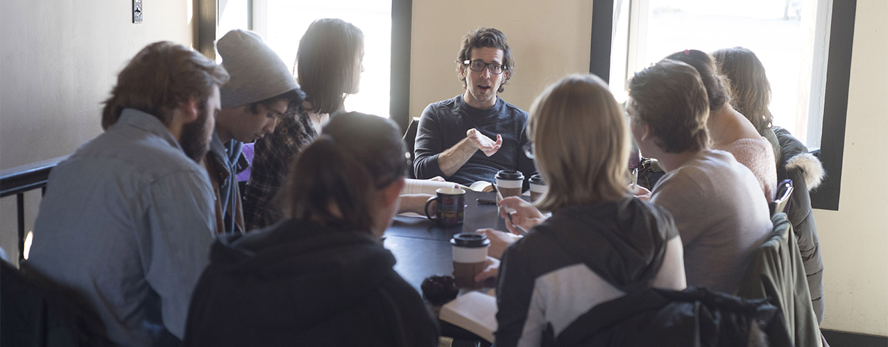 Cedarville University professor teaching a small group of students around a table.