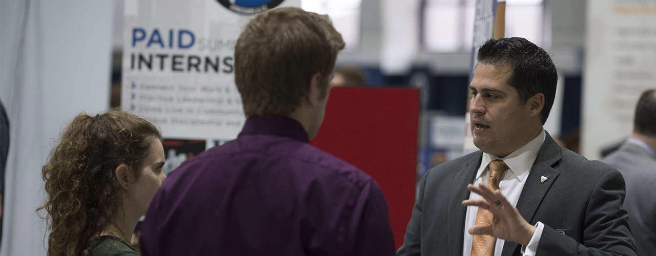 Recruiter talking to two students during a Cedarville University career fair