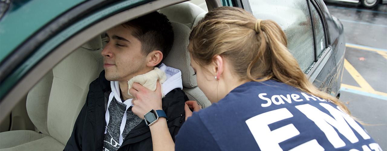 EMT placing a bandage on a patient's neck inside a car.