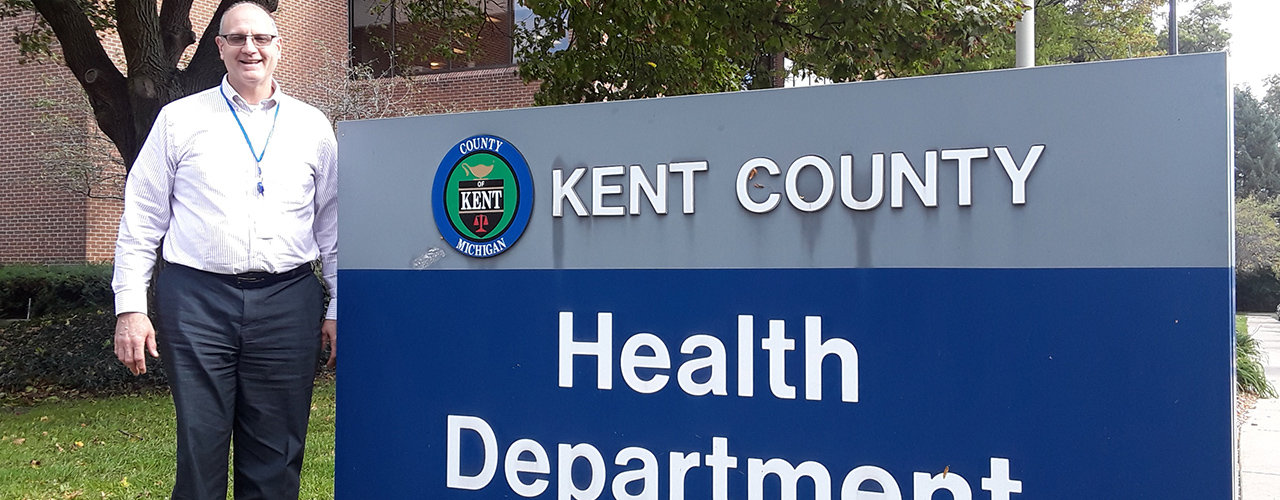 Cedarville alumnus Gary Osantowski standing next to Kent County, Michigan Health Department sign.
