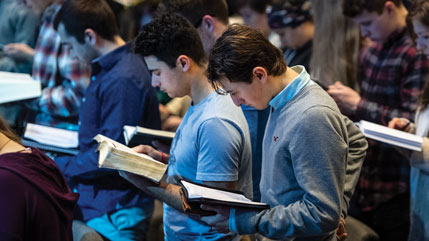 Cedarville students reading Bibles in chapel.