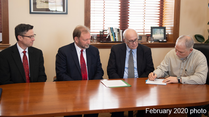 Dr. John Whitmore signing the agreement with the International Conference on Creationism