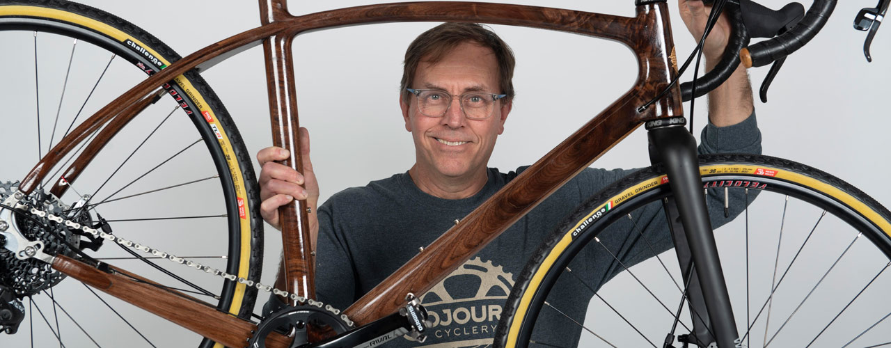 Prof. Jay Kinsinger holding a Sojourn Cyclery wooden bike