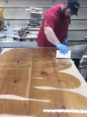 Phil Kochsmeier spreading polyurethane on a table top