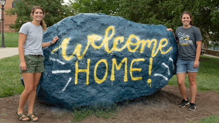 Two friends at the Rock with Welcome Home message spray painted