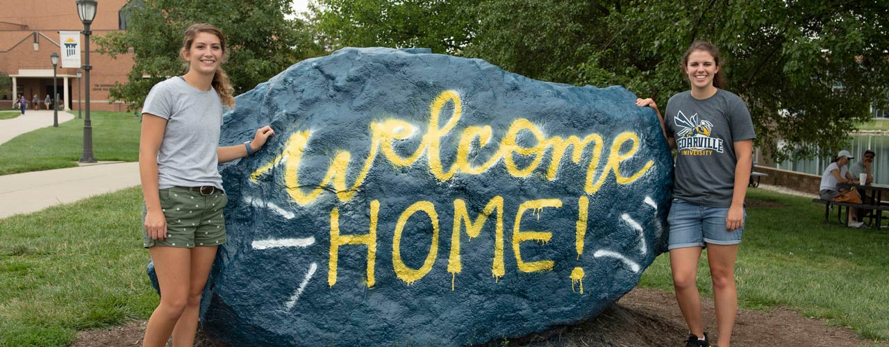 Two friends standing next to the Rock with Welcome Home message spray painted on it.
