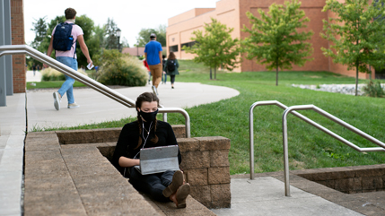 Student working on computer on steps in front of BTS