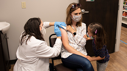 Pharmacist vaccinating a patient with little girl looking on
