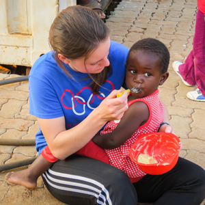 Global Outreach student feeding a toddler girl