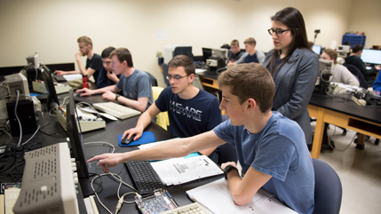 Dr. Danielle Fredette and students looking at computers
