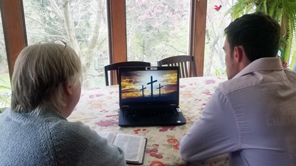 Mom and son looking at a computer screen with three crosses on a hill pictured