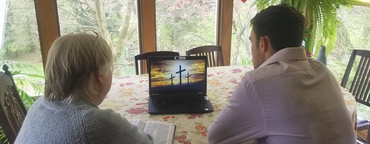 Mom and son looking at computer screen with three crosses on a hill pictured