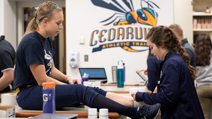Student trainer wrapping an athlete's foot.