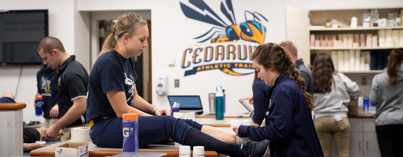 Student athletic trainer wrapping an athlete's foot.