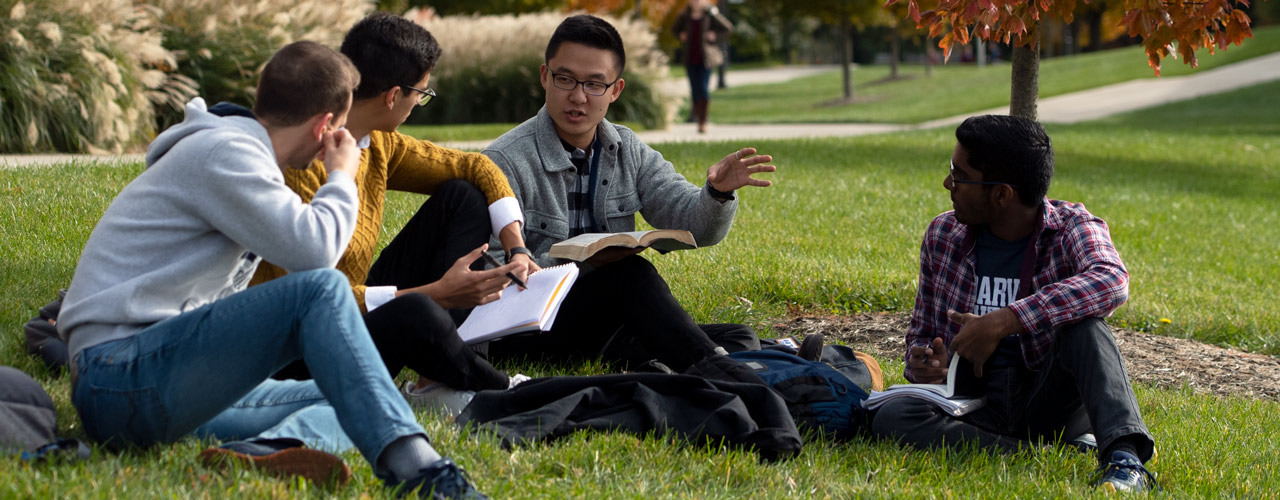 Students discussing the Bible while sitting on the grass