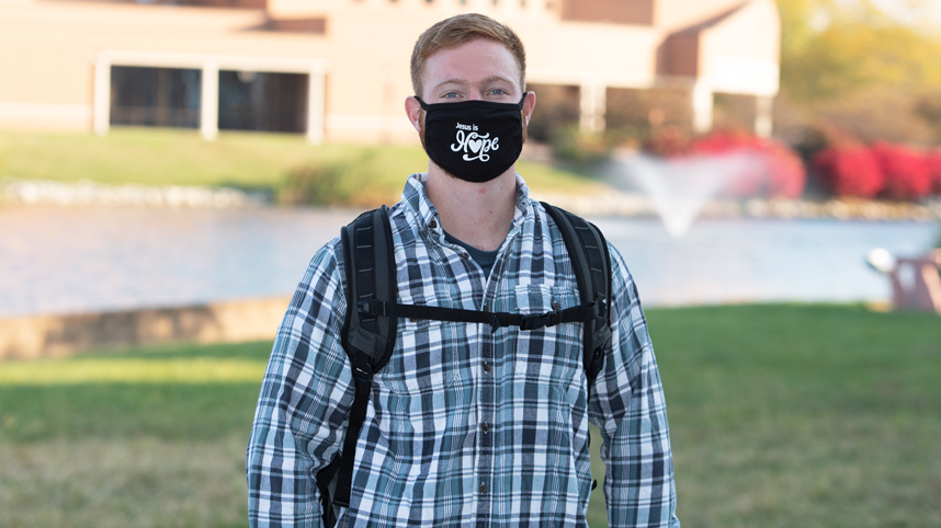 Male student in mask with Cedar Lake and Dixon Ministry Center behind him