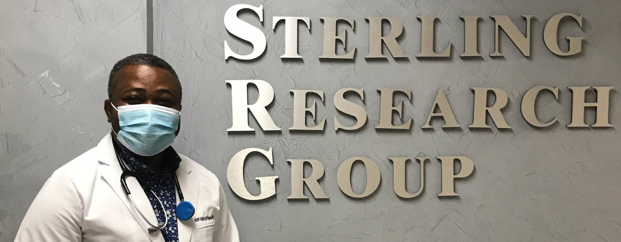 Dr. Kofi Amoah standing in front of Sterling Research Group sign