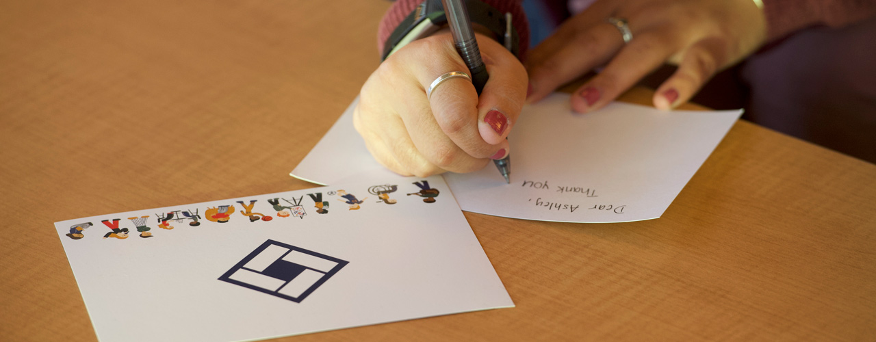 Kelsey Laing writing a note to a classmate