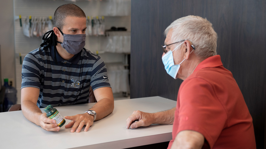 Dr. Thad Franz talking with a patient at Cedar Care Pharmacy