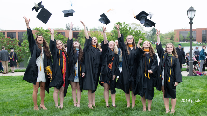 Graduates tossing mortar boards in the air after 2019 Commencement