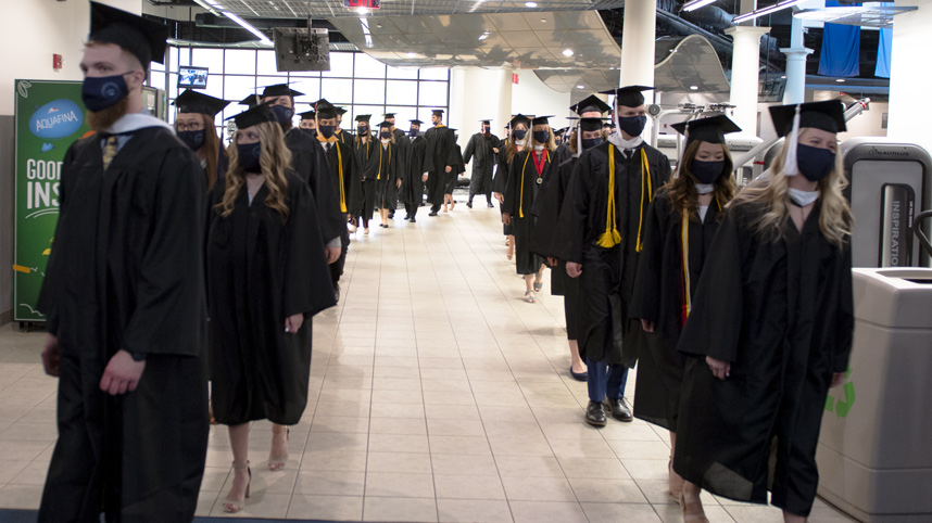 Undergraduate students marching into Doden Field House in two columns