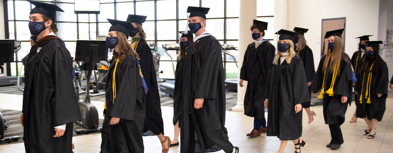 Undergraduate students wearing masks walking into Doden Field House