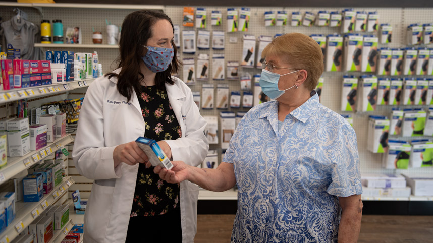 Pharmacy student serving a customer at Cedar Care Village Pharmacy