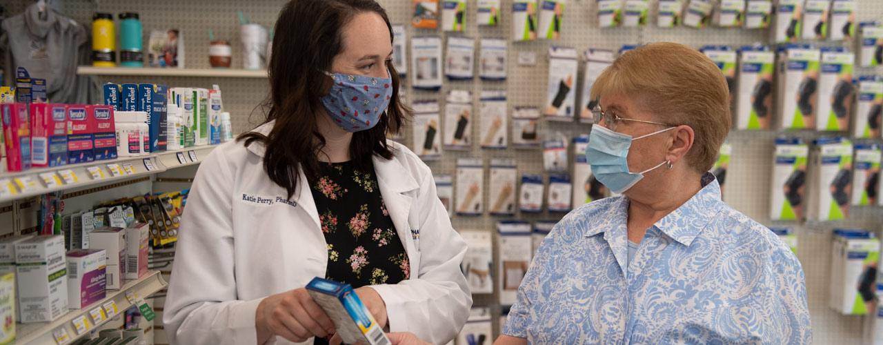 Pharmacy student serving a customer at Cedar Care Village Pharmacy