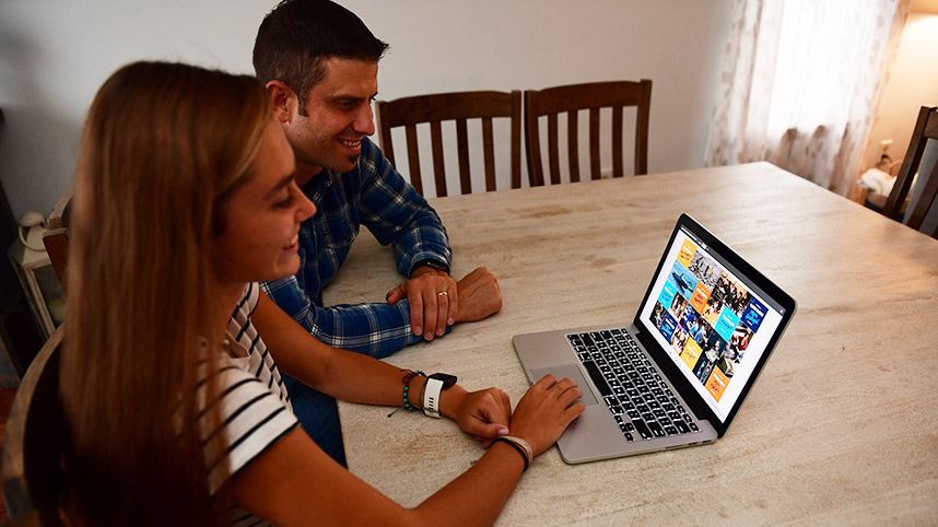 Dad and daughter looking at College Now information on laptop