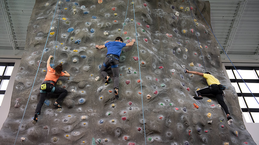 Three students ascending the climbing wall in the Fitness Center