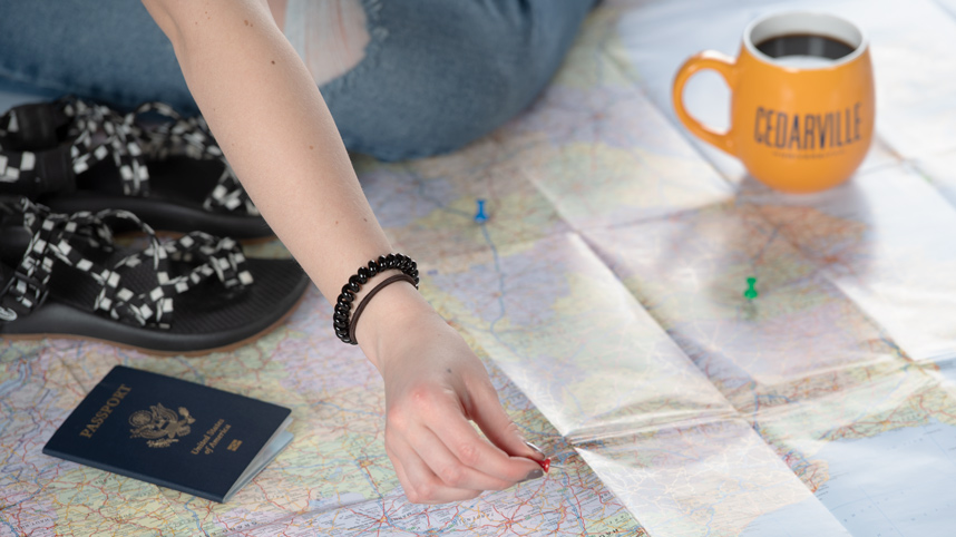 Student's hand placing pin on a map with a passport laying nearby