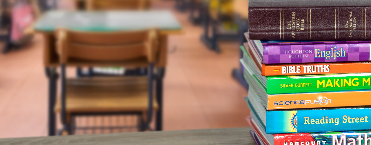 Stack of schoolbooks with Bible on top