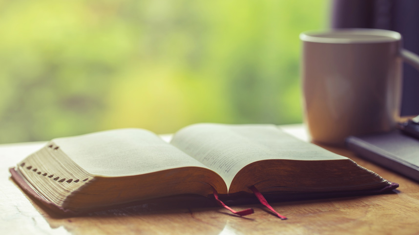 Open Bible with a cup of coffee on a table and greenery in the background