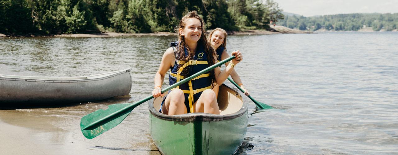 Two teenage girls paddling a canoe