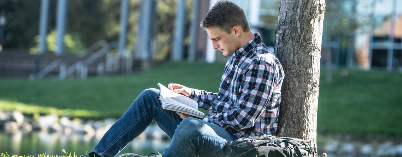 Student sitting on the campus grass and reading a book