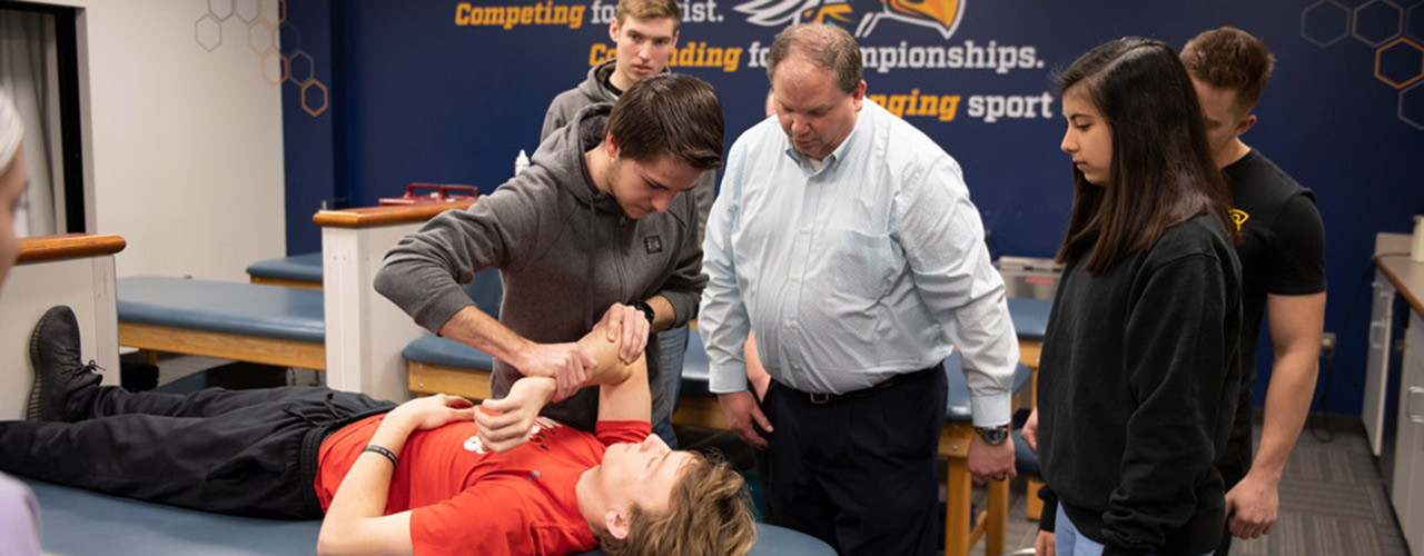 Professor Mike Weller instructing athletic training students in a lab.