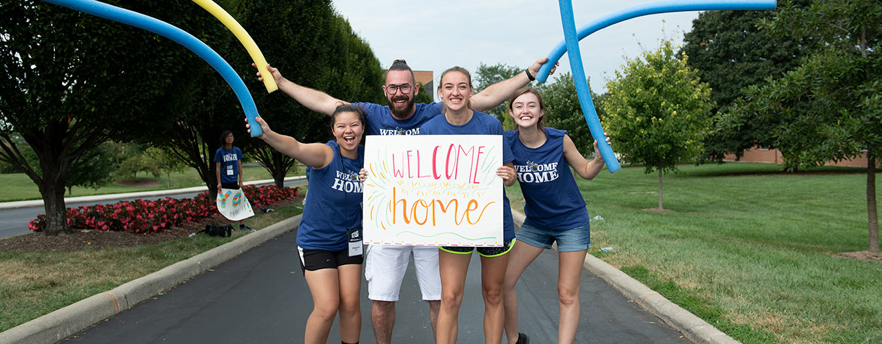 Four students in purple Welcome Home shirts holding a Welcome Home sign and pool noodles