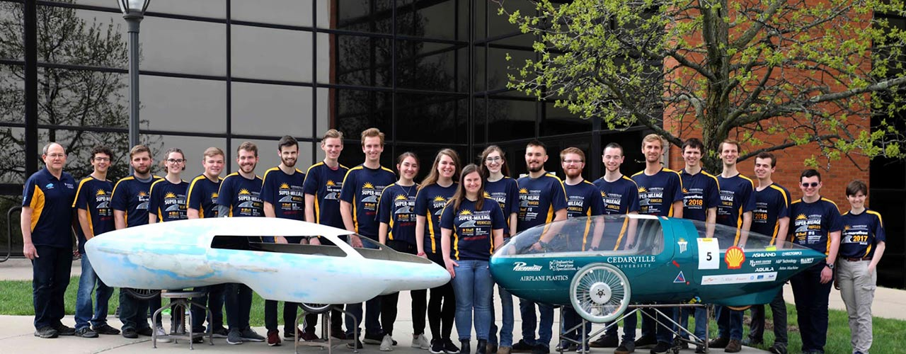"""Cedarville's engineering team with the cars they designed for the SAE Supermileage (left; nicknamed """"Karcharias"""") and Shell Eco-Marathon (right; nicknamed """"Sting"""") competitions."""
