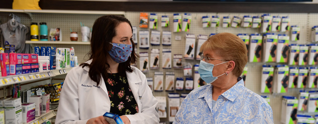 Dr. Katie Perry serving a patient at Cedar Care Village Pharmacy