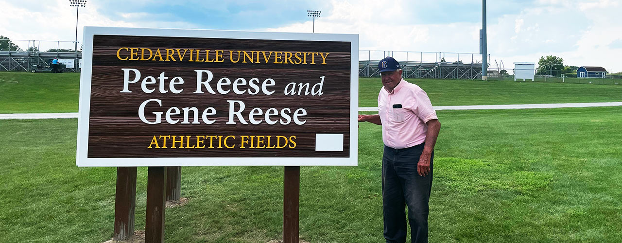 Pete Reese standing next to the new Pete Reese and Gene Reese Athletic Fields sign
