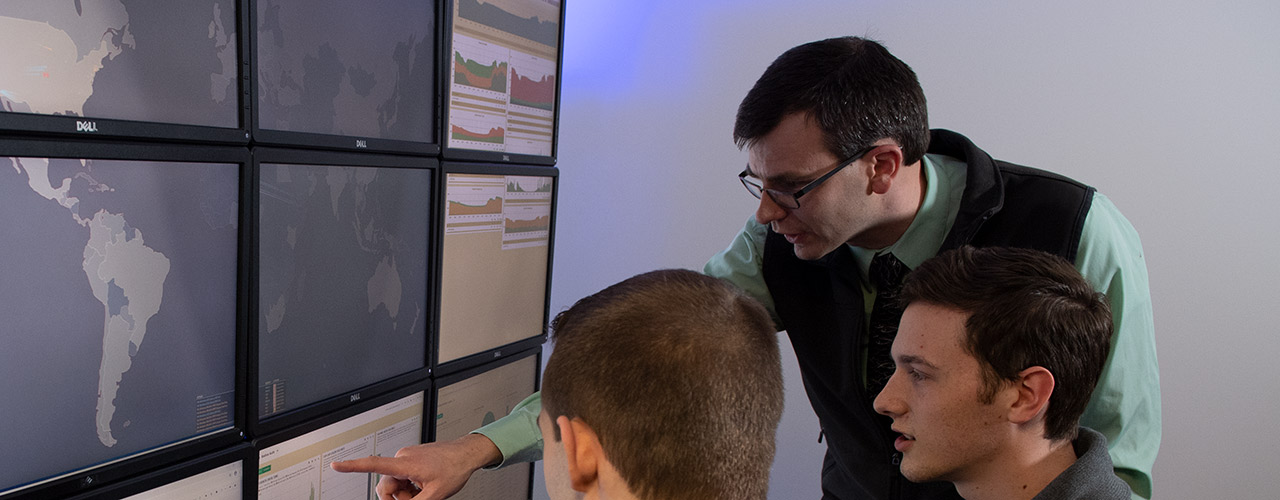 Professor Patrick Dudenhofer instructs students in the cyber lab