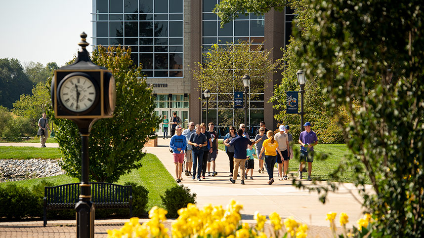 Admissions tour guides walk a group between the health sciences center and Stevens Student Center.