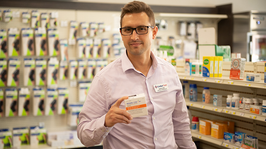 Dr. Justin Coby, director of Cedar Care Village Pharmacy, holding a box of monoclonal antibodies