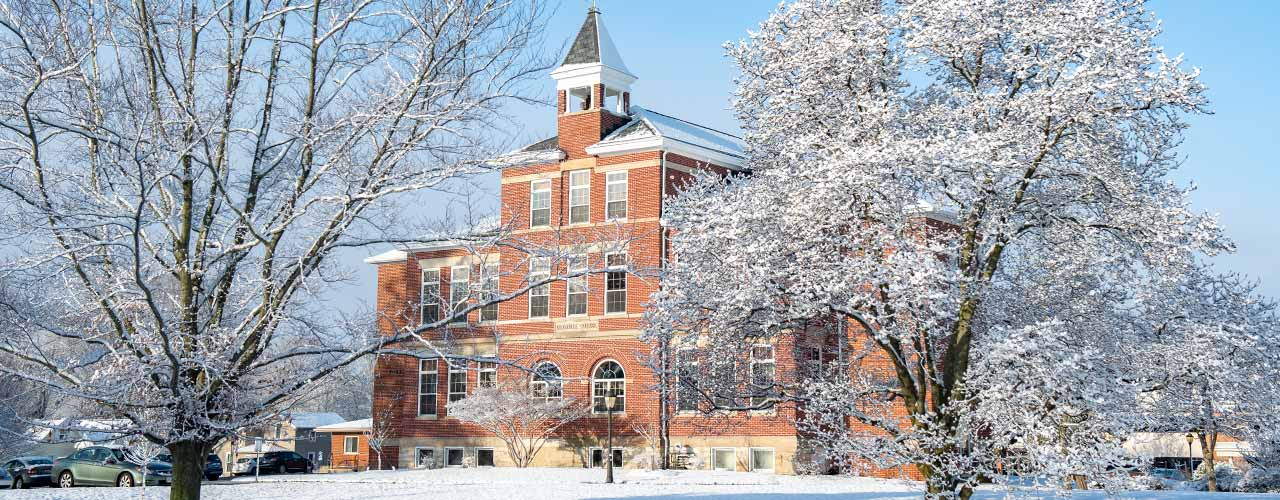 Winter scene with snow covered trees and Founders Hall.